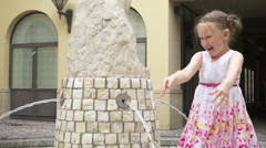 A little girl throws water from a public fountain in the air and laughs. 120fps Stock Footage