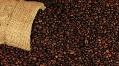 Young man puts a cup of coffee on roasting coffee beans on brown wooden table Stock Footage