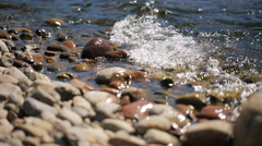River waves beating against coastal rocks making them wet Stock Footage