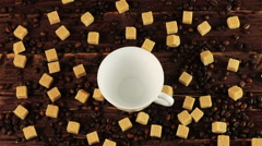 Coffee is poured into a white cup on the table on him located coffee beans and Stock Footage