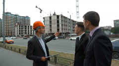 Architector in helmet presents to customers their building Stock Footage