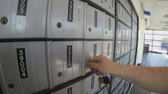 Close Up Of Man Unlocking Post Office Box And Retreiving Mail - stock footage