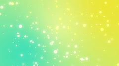 Sparkly light particles moving across a teal yellow gradient background - stock footage