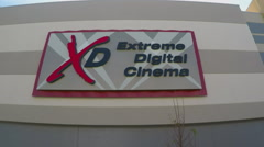Extreme Digital Cinema Sign On Theater Building - Close Up Stock Footage