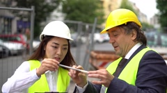 Expert engineer showing young Asian colleague an instrument - stock footage