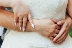 Hands and rings on a body of fat bride Stock Photos