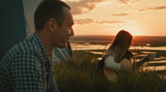 Young attractive girl with friends plays acoustic guitar in camping outdoors on - stock footage
