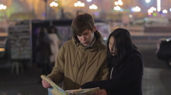 Male and female tourists lost in city and looking on map, searching for a place Stock Footage