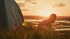 Man tunes acoustic guitar in camping outdoors on high hill at summer sunset Stock Footage