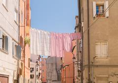 Sheets hanging to dry across a street of Naples. Stock Photos