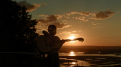 Landscape at sunset with kid and music: boy having fun and play guitar Stock Footage