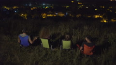 The people sit and talk near the tent on the background of the night city - stock footage