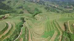 AERIAL FLY OVER RICE TERRACE FARMER SPRAYING PESTICIDES ON HIS CROPS IN CHINA Stock Footage