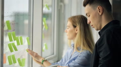 Two office workers glue colorful stickers on window - stock footage