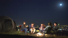The people sit and talk near the tent on the background of the night city Stock Footage