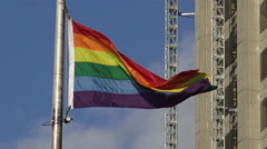 Pride flag waving with the wind against blue sky Stock Footage