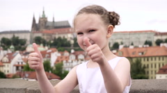 A little girl dressed in white clothes thumbing up and smiles shyly in Prague. Stock Footage
