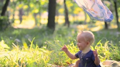 Mom plays with one year old baby girl with shawl, covering her on a green meadow Stock Footage