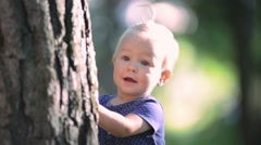 Baby girl one year old playing hide and seek, hiding behind a big tree - stock footage