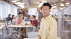 4K Portrait of smiling businessman in office with staff working in background Stock Footage