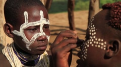 Close Up of Young Boy From Omo Valley Tribe Doing Traditional Dot Face Painting Stock Footage
