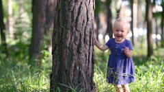 Baby girl one year old playing hide and seek hiding behind a big tree, laughs - stock footage