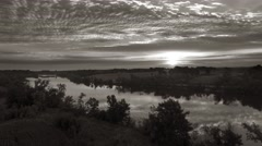 Dramatic sunrise over river, black and white aerial view. Stock Footage