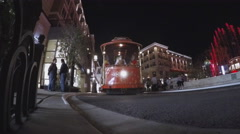 Low Angle Trolley Car Train At Outdoor Shopping Center At Night Stock Footage