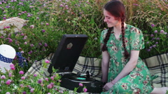 Young girl on picnic in the meadow listening to the record on vintage gramophone - stock footage