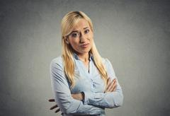 grumpy skeptical blonde woman isolated on gray background - stock photo