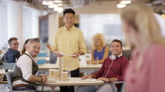 4KPortrait smiling businesswoman in office with colleagues working in background - stock footage