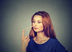 Woman with long nose isolated on grey wall background. Liar concept Stock Photos