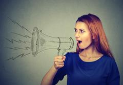 Angry young woman screaming in megaphone Stock Photos