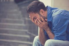 Stressed sad young crying man sitting outside holding head with hands Stock Photos