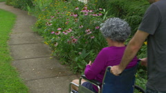 Pushing old woman in wheelchair wheel chair Stock Footage