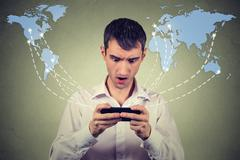 Surprised man holding smartphone connected browsing internet Stock Photos
