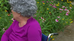 Senior citizen in wheelchair look garden Stock Footage