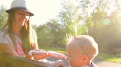 Mom with a one year old baby girl playing pat-a-cake on a park bench Stock Footage