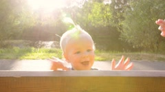 One year old baby girl having fun and playing pat-a-cake on a park bench Stock Footage
