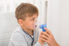 Close-up Of A Little Boy Inhaling Through Oxygen Mask In Clinic - stock photo