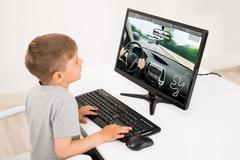 Little Boy Playing Car Game On Computer At Home - stock photo