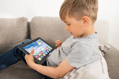 Boy Using Digital Tablet With Multicolored Apps On It - stock photo