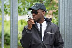 Young Male Security Guard In Black Uniform Using Walkie-Talkie - stock photo