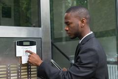 Young African Businessman Entering Code In Security System - stock photo