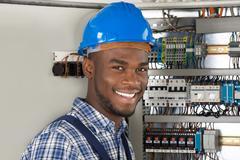 Male Technician Holding Clipboard While Examining Fusebox Stock Photos