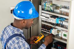 Young African Male Technician Examining Fusebox With Multimeter Probe Stock Photos