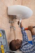 Young African Male Plumber Lying On Floor Fixing Sink In Bathroom Stock Photos