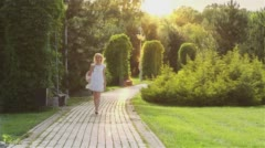 Beautiful girl walking alone in the park at sunset 1 with sun glare Stock Footage