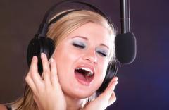 Woman singing rock song microphone headphones Kuvituskuvat