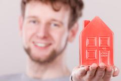 Young man holding house on palm. - stock photo